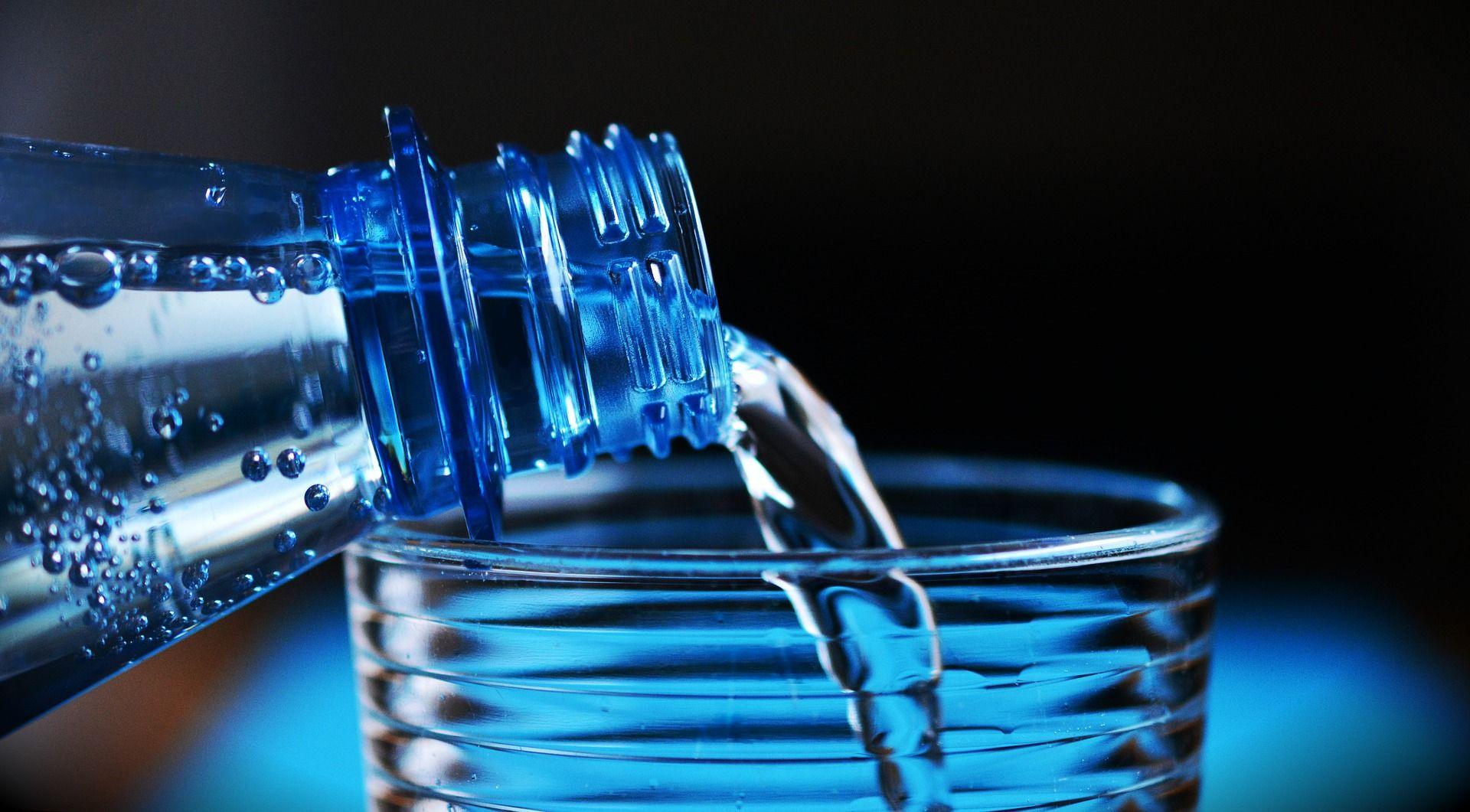 Botella vertiendo agua en un vaso